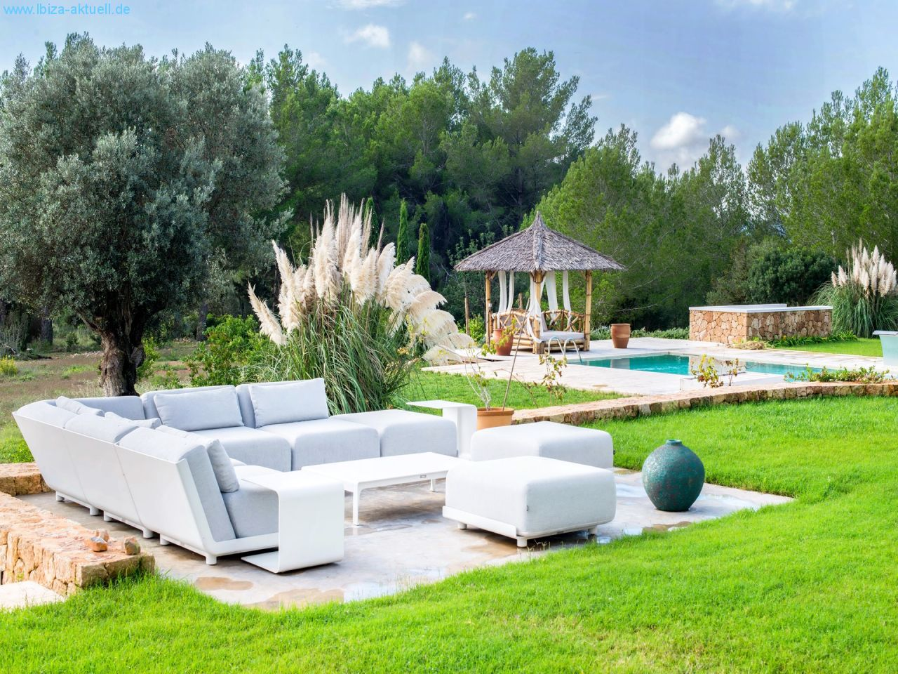 modern sofagroup on the terace infront of the house and large lawn